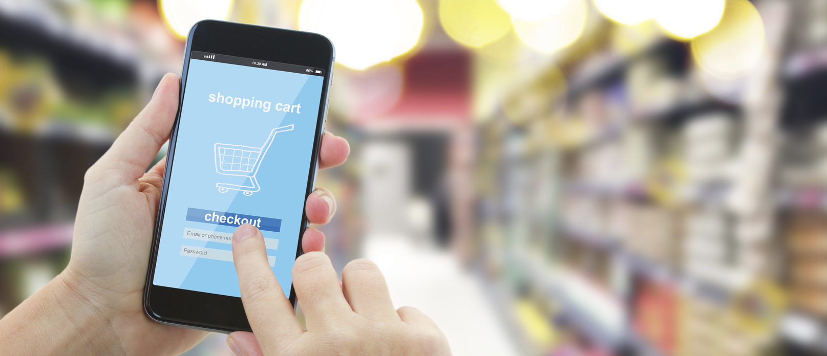 woman hands holding mobile smart phone with mobile shop on supermarket blur background - e-commerce concept